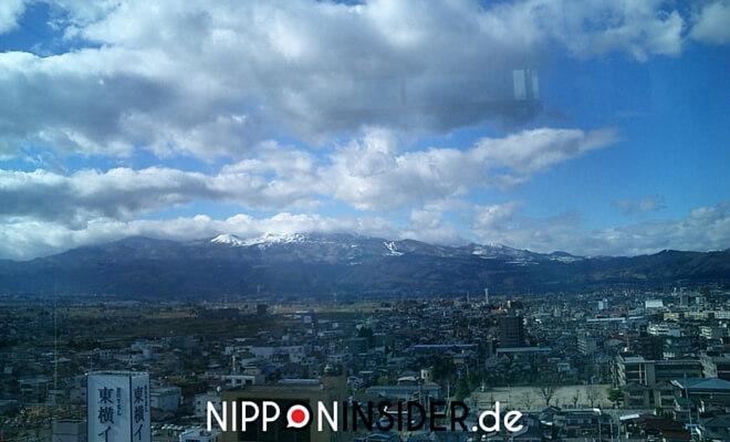 Mein Fukushima ist Die Stadt Fukushima. Schneebedeckte Berge im Hintergrund. BlauerHimmel mit tollen Wolken