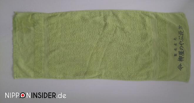 Towel Day: Ein grünes Handtuck als Werbegeschenk mit Aufdruck | Nipponinsider