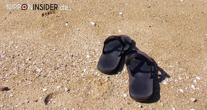 Schwarze Flip-Flops am Strand als Tipp für die Regenzeit in Japan | Nippon Insider Japan Blog
