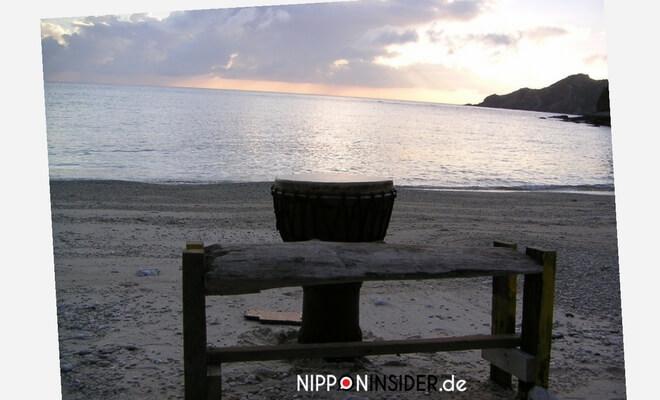 Sonnenuntergang am Strand mit einer Trommel und einem Baumstamm als Sitzbank. Inselabenteuer auf Okinawa, Akajima | Nipponinsider