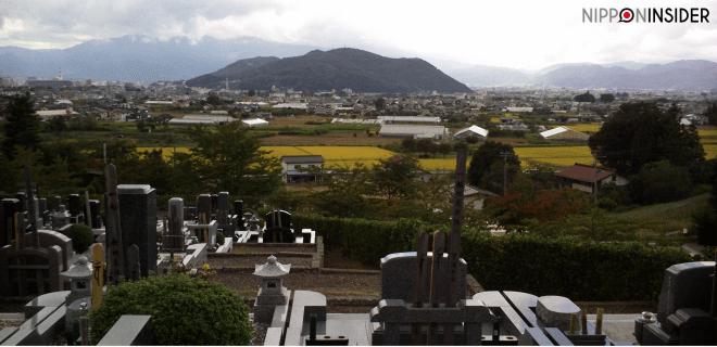 Friedhof am Rande von Fukushima mit Blick auf einen Berg und auf die Stadt. Im Vordergrund Grabsteine | Nipponinsider Japanblog