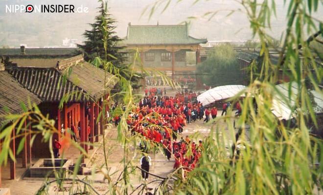 Die Whushu School of Shaolin Kung Fu in China. Viele Kungfustudenten auf dem Campus der Schule mit roten Jogginganzügen | Nipponinsider