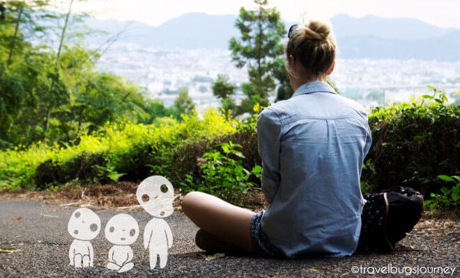 Tara erzählt: Warum ich Japan liebe. Im Schneidersitz mit Blick auf japanische Stadt und Waldgeister neben sich.