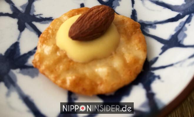 japanischer Käse-Reis-Cracker mit einer Mandel garniert. Senbei