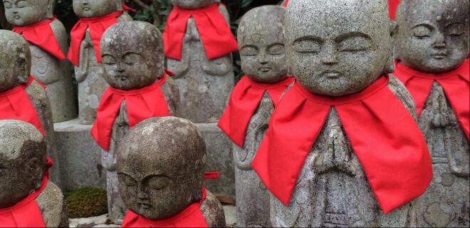 japanische Jizo Statuen mit roten Lätzchen