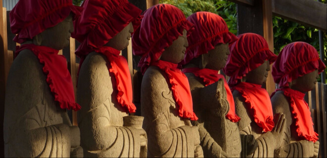 japanische Statuen mit roter Mütze und Lätzchen - Jizo