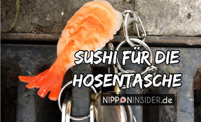 Sushi für die Hosentasche. Bild von einem Stück Sushi mit Garnele an einem Schlüsselbund auf einem Gulli | Nipponinsider