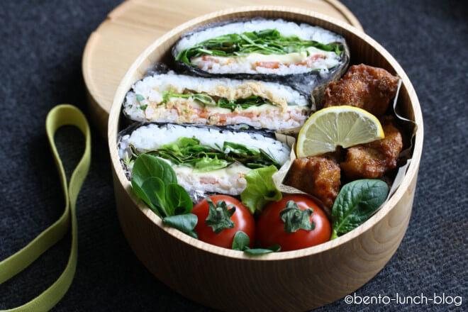 Runde Lunchbox aus Holz mit frittierten Hähnchen, Onigiri und Tomate. Foto von Token Bento-Lunch-Blog