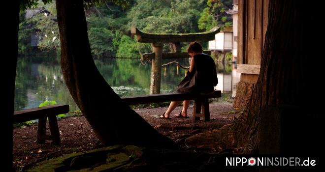 Wie oft reist ihr nach Japan? FAQ: Vor einem See sitzende Frau in Japan | Nipponinsider