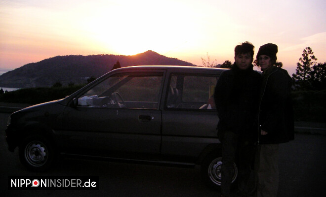 Flitterwochen in Japan vor dem Auto stehend, im Hintergrund der Sonnenaufgang | Nipponinsider
