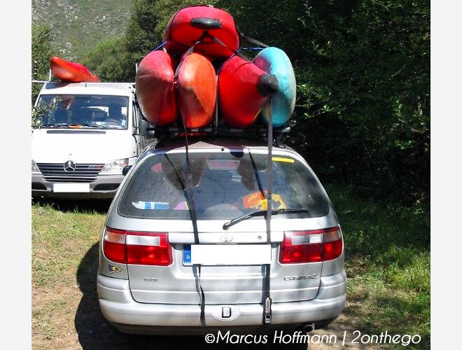 Toyota Carina mit fünf Kanus auf dem Dach