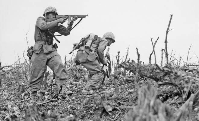 schwarz-weiß-Foto von Soldaten auf Okinawa während des zweiten Weltkrieges. Ein Soldat hält ein Gewehr in die Luft zum Schuss bereit.