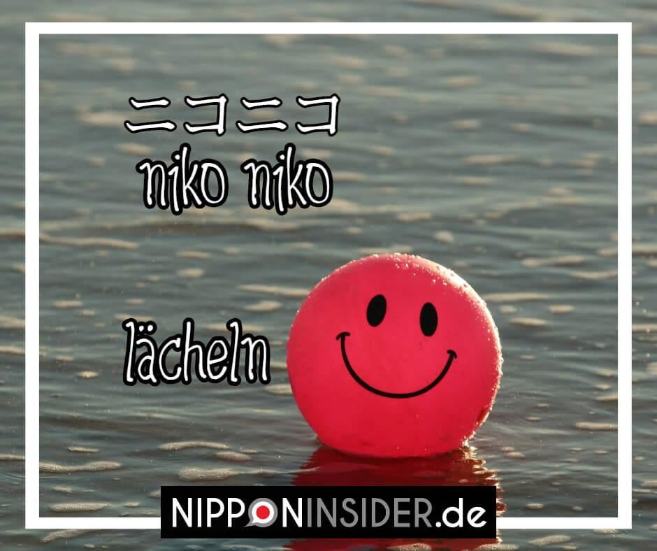 Bild eines Balles mit einem Smiley aufgemalt im Wasser schwimmend. Text: niko niko ist umgangsprachliches Japanisch und bedeutet: lächeln. Japanische Ausdrücke auf Nipponinsider